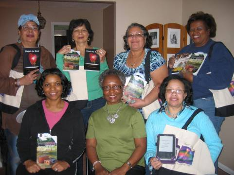 Members of Read n Play Book Club display copies of Simpson's books and their custom-designed book totes